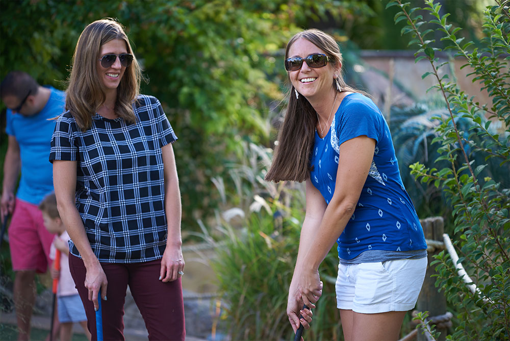 Two women playing mini golf