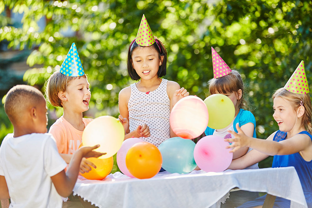 young children celebrating birthday with balloons